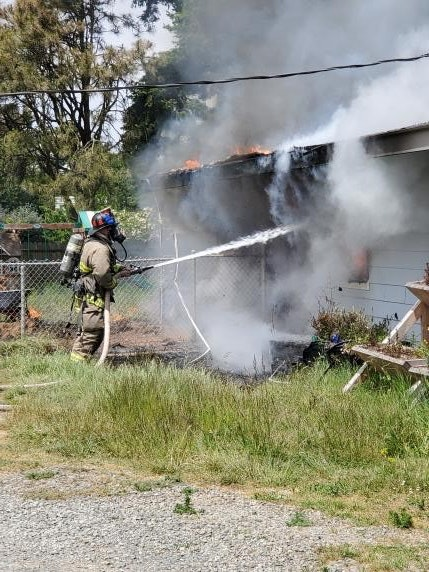 Firefighter squirting water on a burning home
