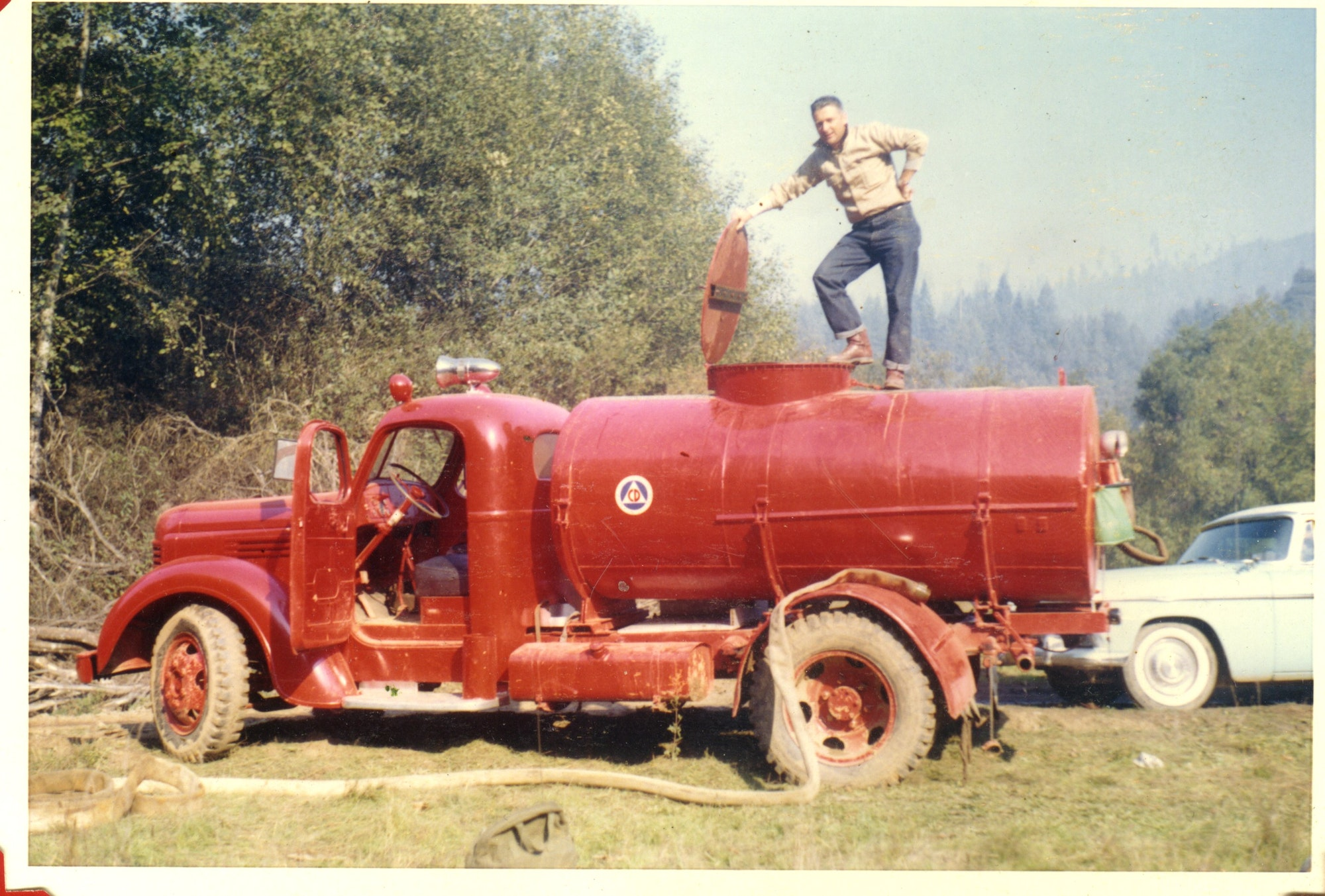 Photo of person on top of Old Water Tender 8 at an incident.