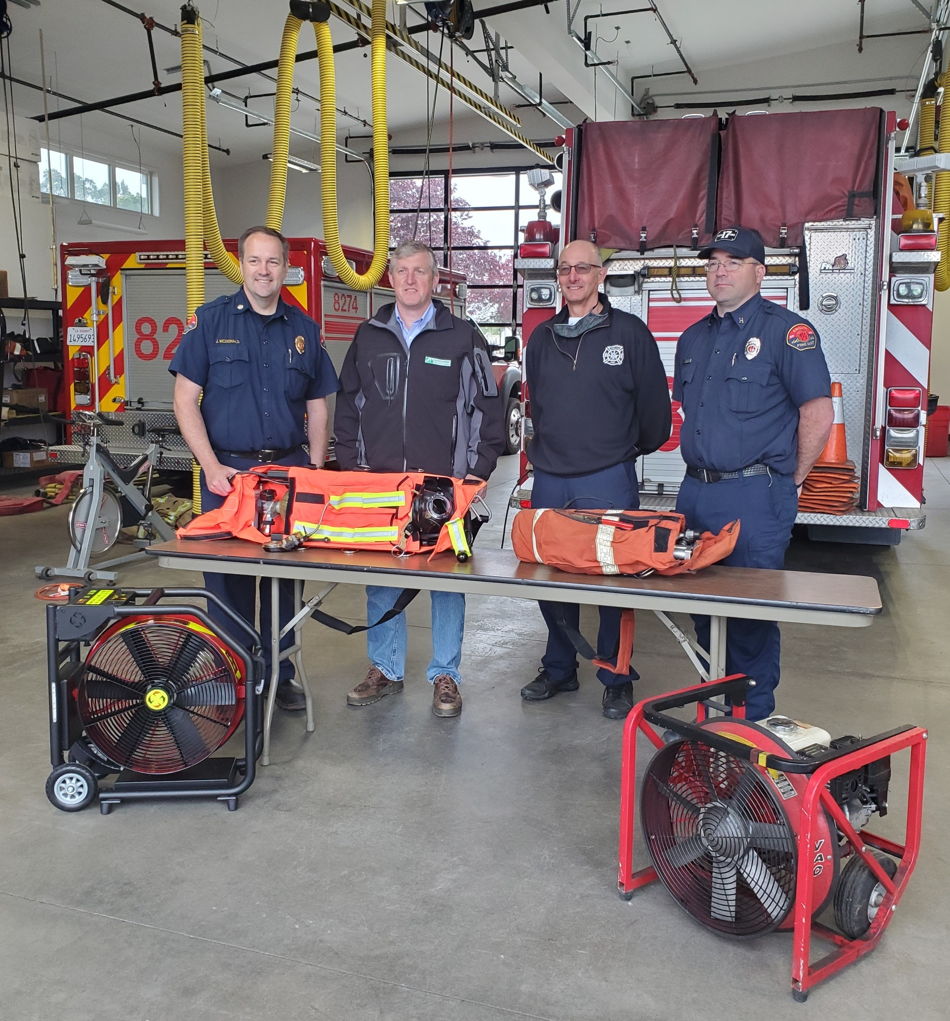 Four adult males with newly donated fire fighting equipment