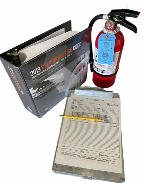 Fire Code binder with an inspection book and extinguisher.