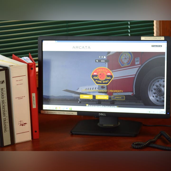 Photo of a monitor on a desk with binders.