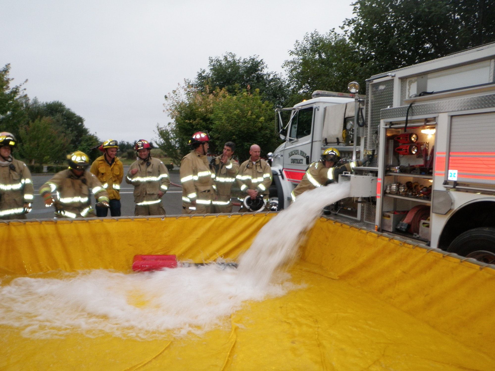 Group of firefighters observing Water Tender filling a portable tank.