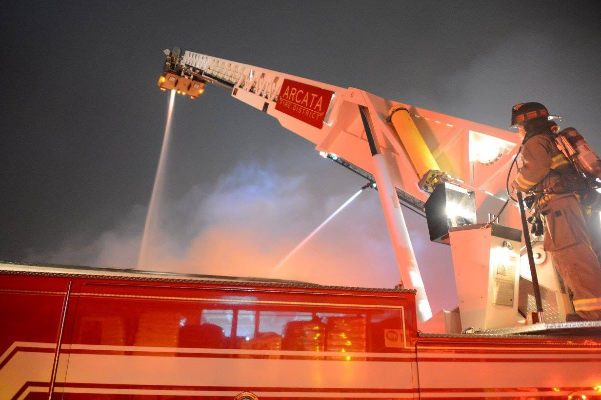 Fire fighter operating a ladder truck master stream.
