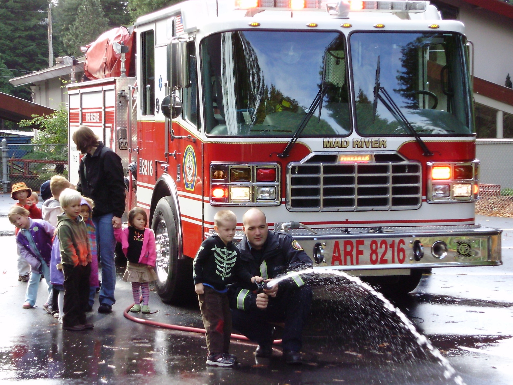 Photo of Firefighter spraying water with kids at public education event.