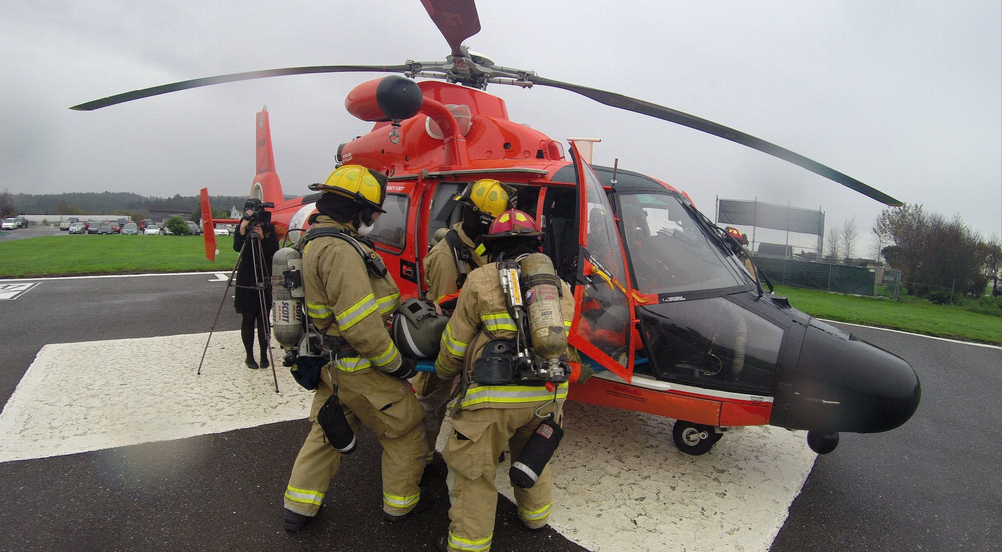 Firefighters loading a patient into a Coast Guard helicopter.