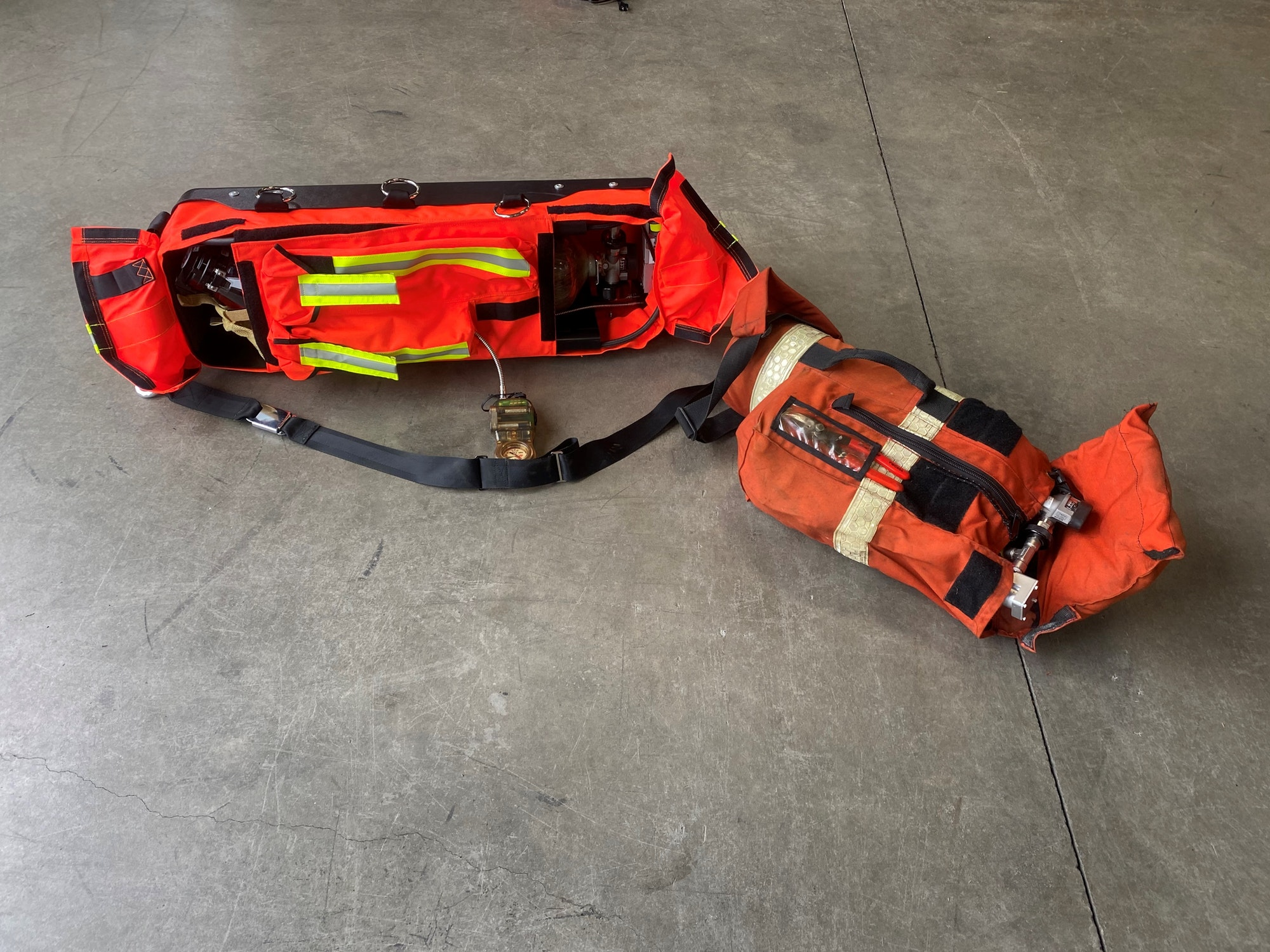 Old and new bright orange bags containing life saving fire equipment