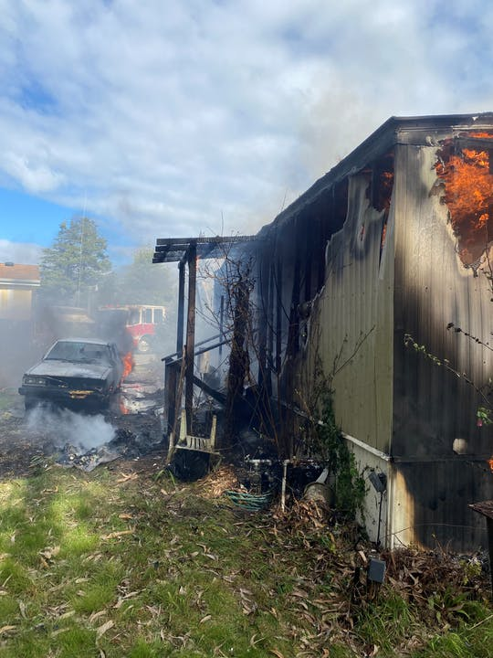 Vehicle next to mobile home on fire