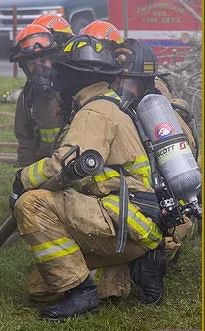 Photo of firefighter leading some recruits in training.