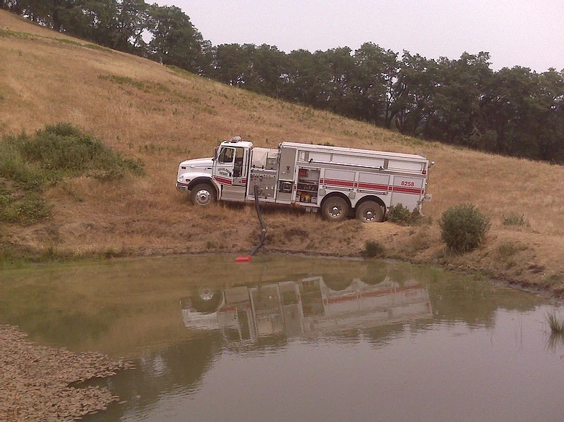 Water tender drafting from a pond.