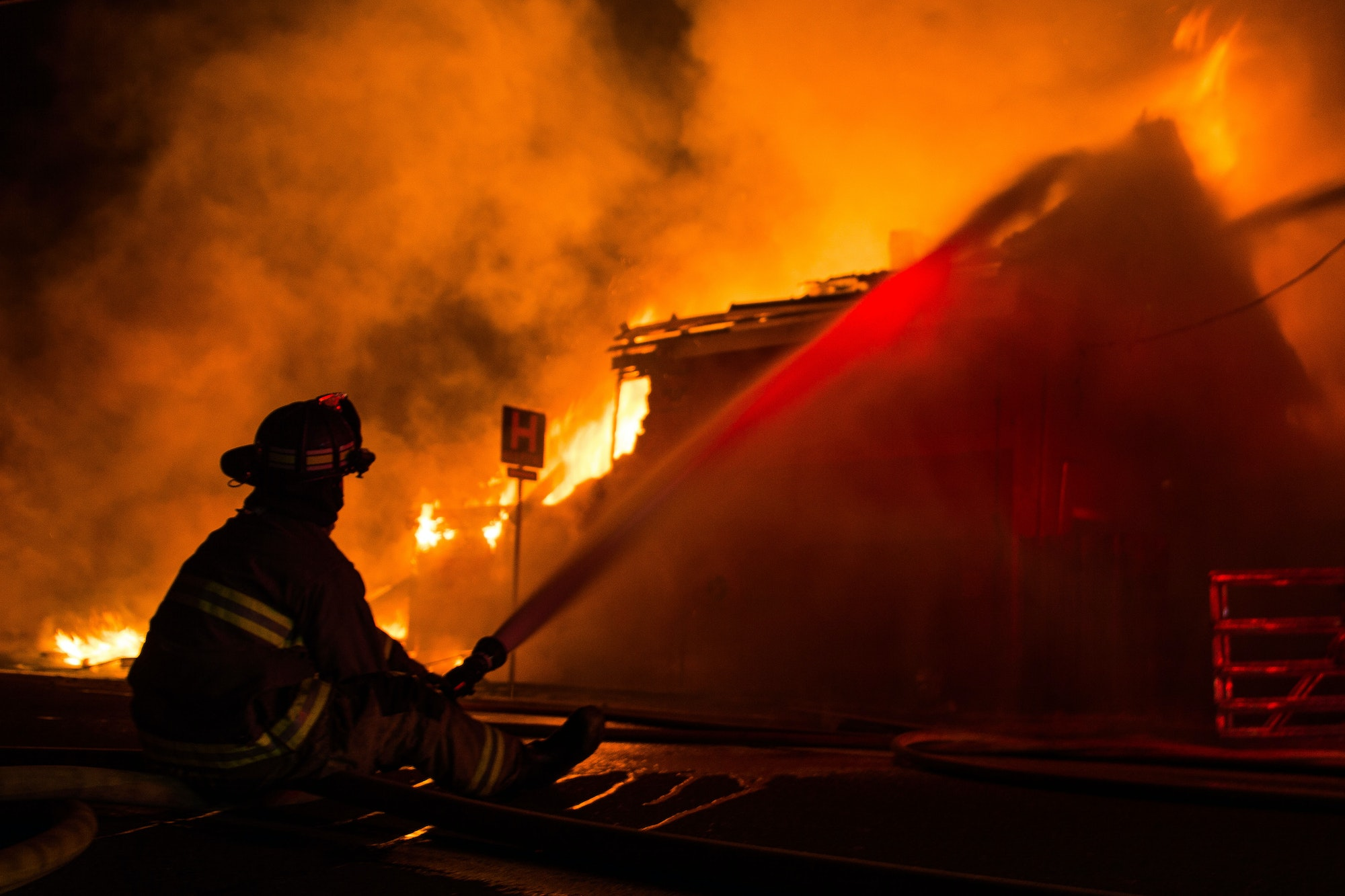 Color photo of a fire fighter directing a hose stream on a structure fire.