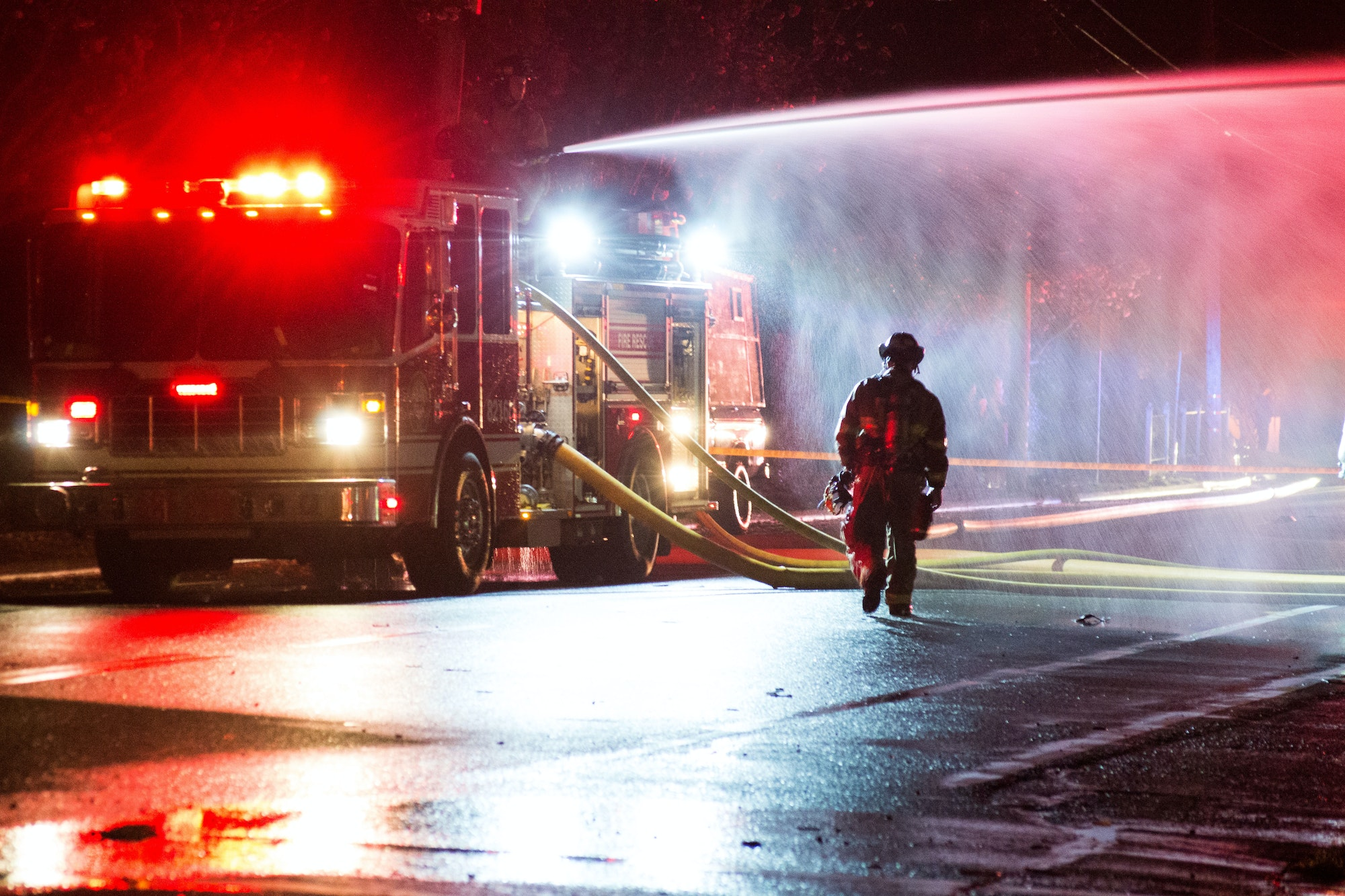 Fire fighter walking next to a pumper at night.