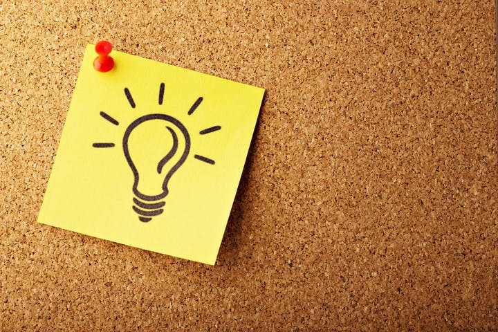Corkboard with a post-it note with an idea lightbulb.