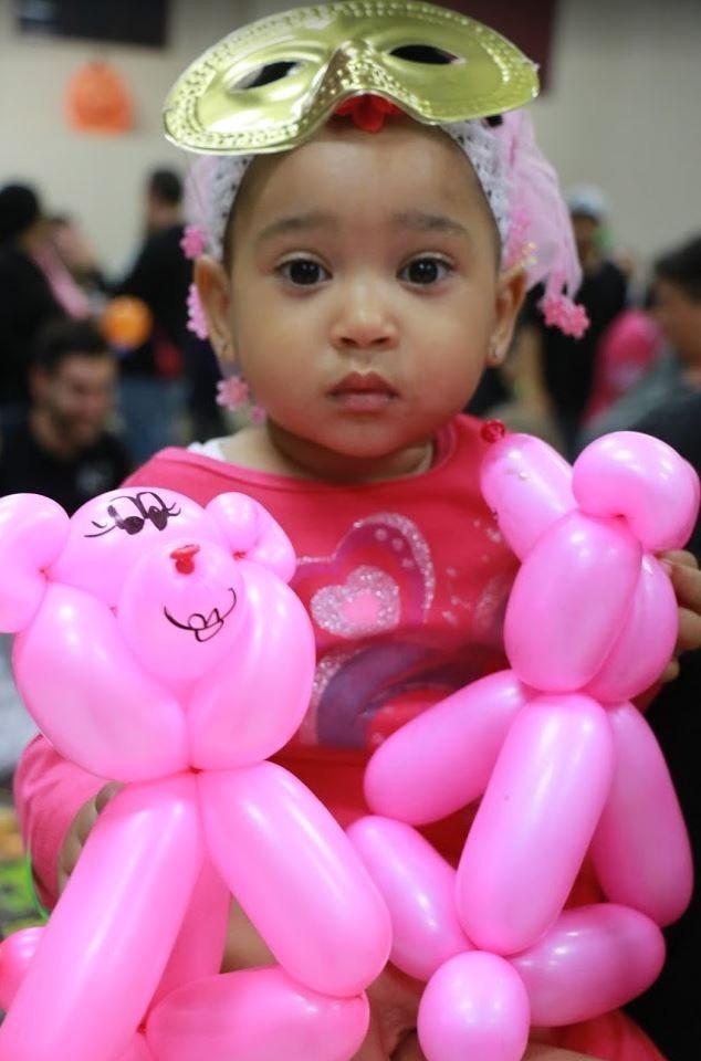 Girl in Halloween costume and a balloon animal