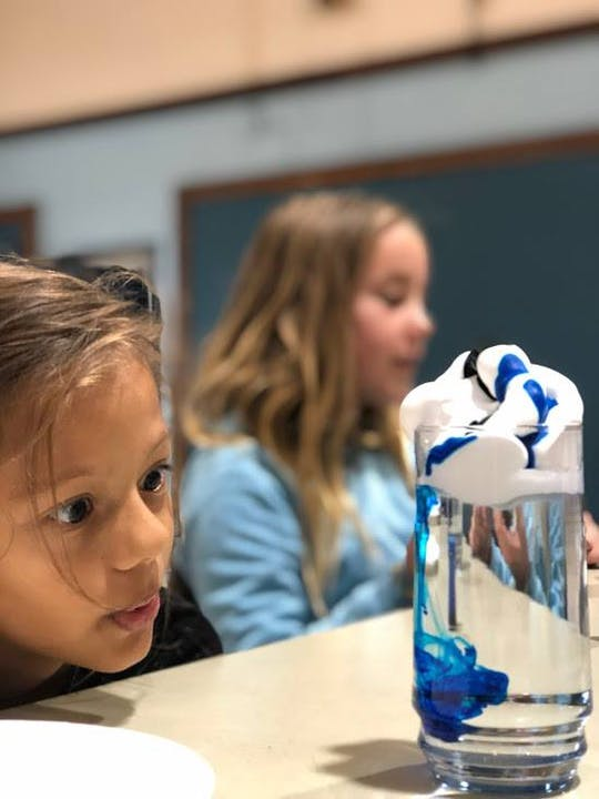 Student watching a water and shaving cream experiment