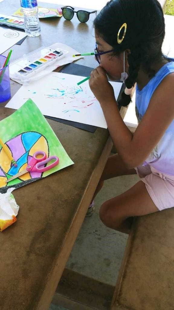 Participant blowing water color on paper to create abstract art.