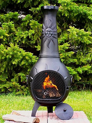 Black chimnea with fire burning, placed on cement pavers