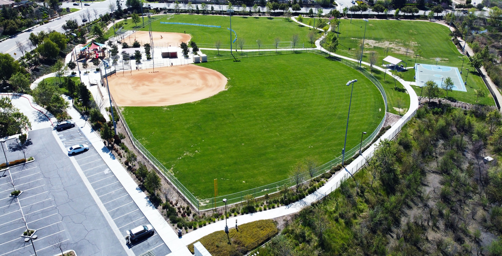 Spencer's Crossing Park, contains baseball fields, grass, basketball court, parking lot, playground, sidewalk