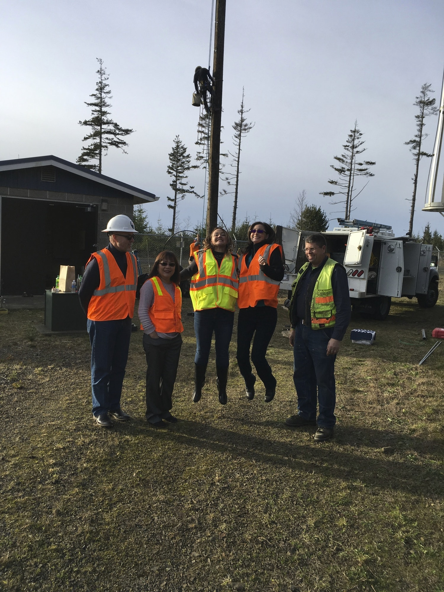 Seal Rock Water District staff with safety equipment on with two employees jumping in air