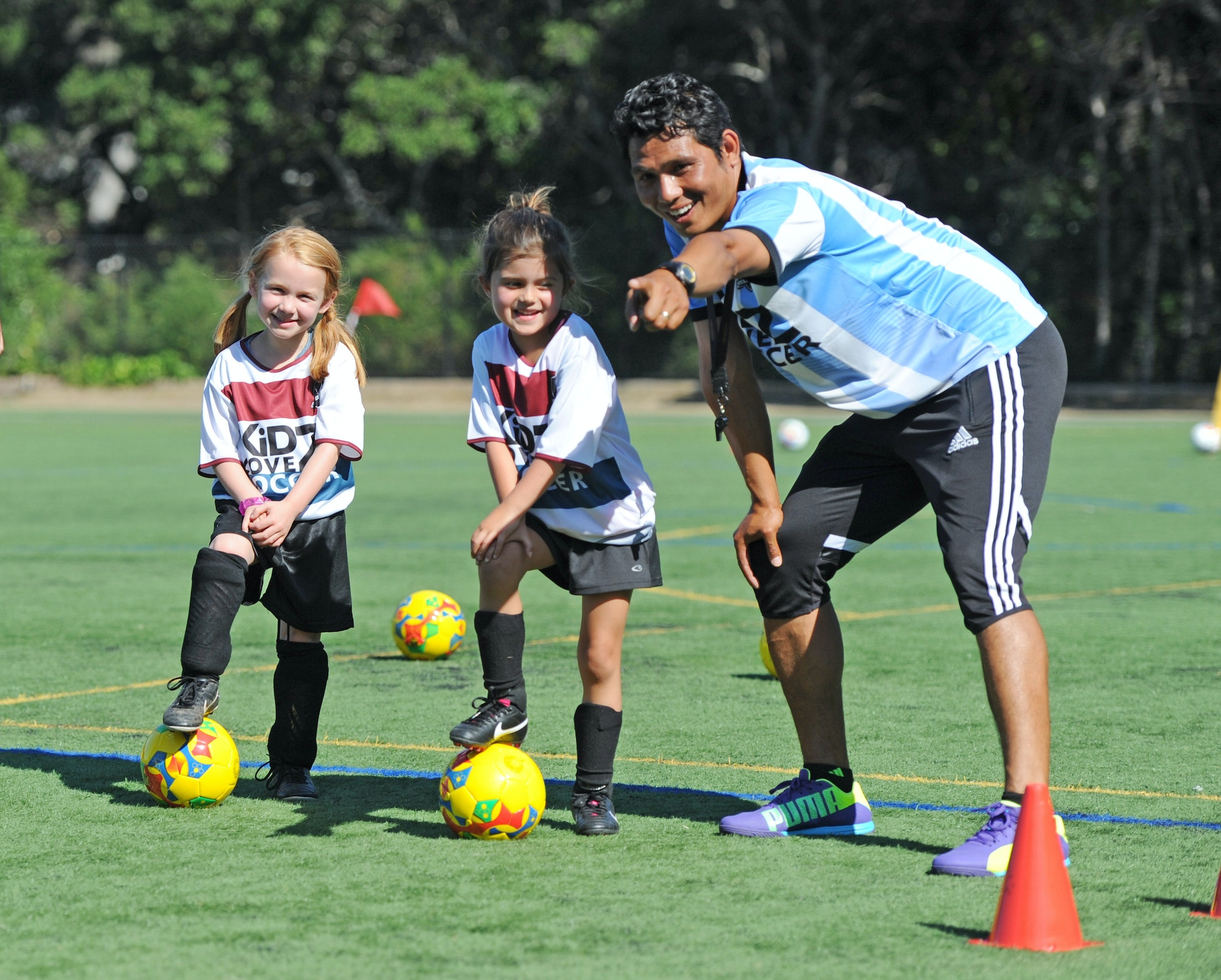 Kidz Love Soccer: Two girl soccer players with foot on balls and coach leaning over and pointing something out to them.