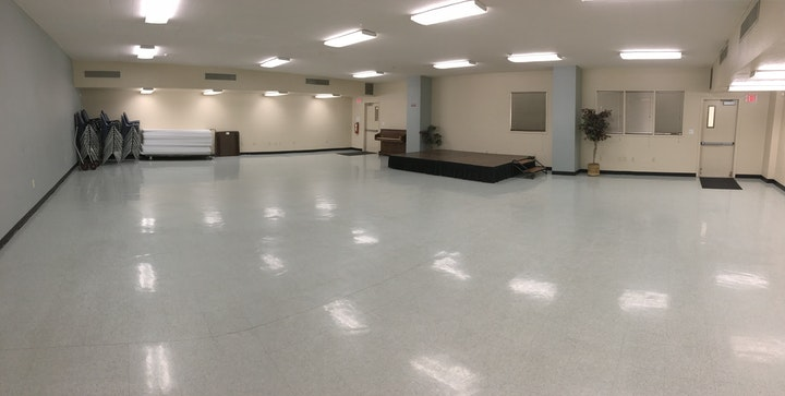 Cypress Room: Mid-Size Room with white tile floor, small stage against a wall, tables and chairs.