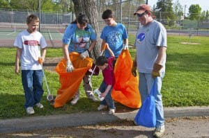 Adopt-A-Park: Children and adults picking up trash and putting it in two trash bags