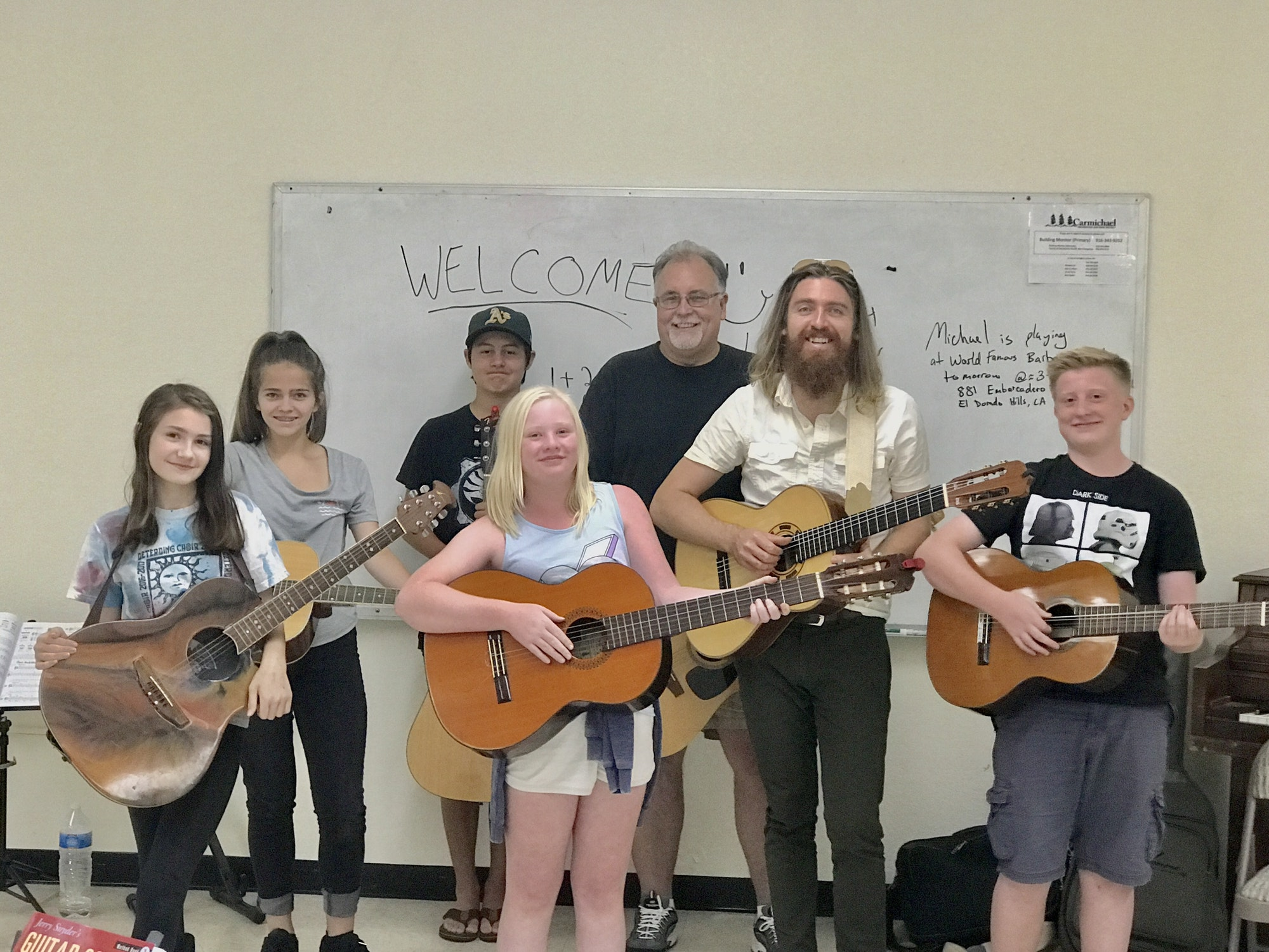 Guitar class: Six students and one instructor all holding their guitars.
