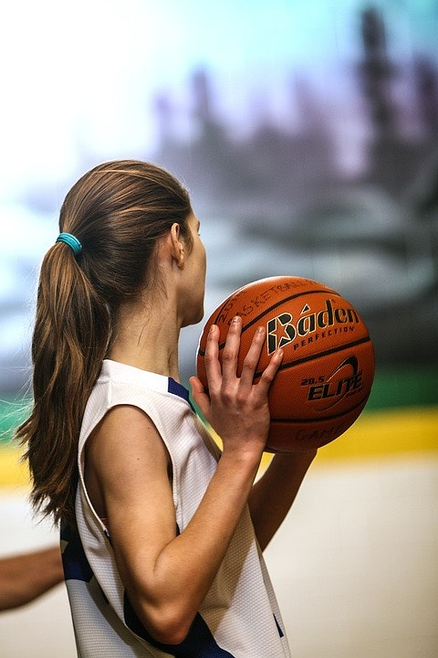 girl in basketball uniform holding a basketball looking away from camera.