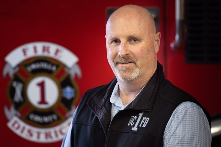 Contains a man named Scott Stanton sitting in front of a red fire engine.