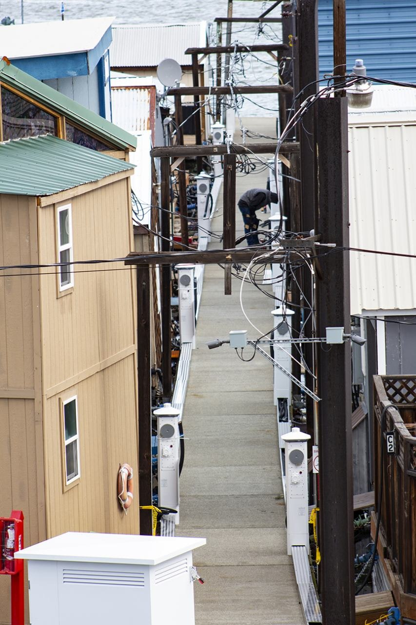 A worker in an alleyway of buildings on the Dalles Marina