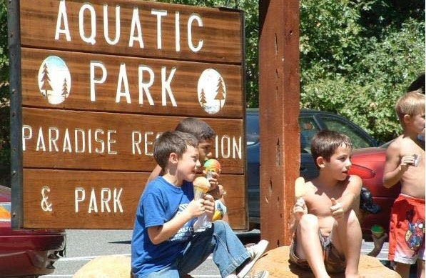 children eating ice cream next to a large wooden Aquatic Park sign