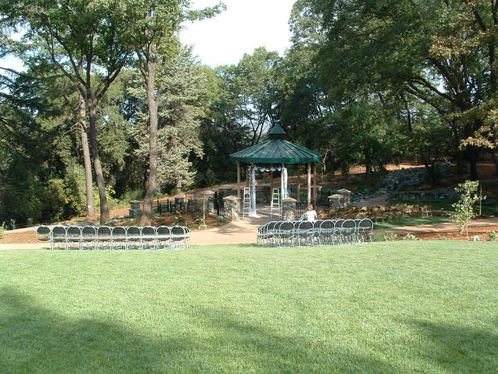 large lawn area with chairs set up in front of gazebo decorated for a wedding