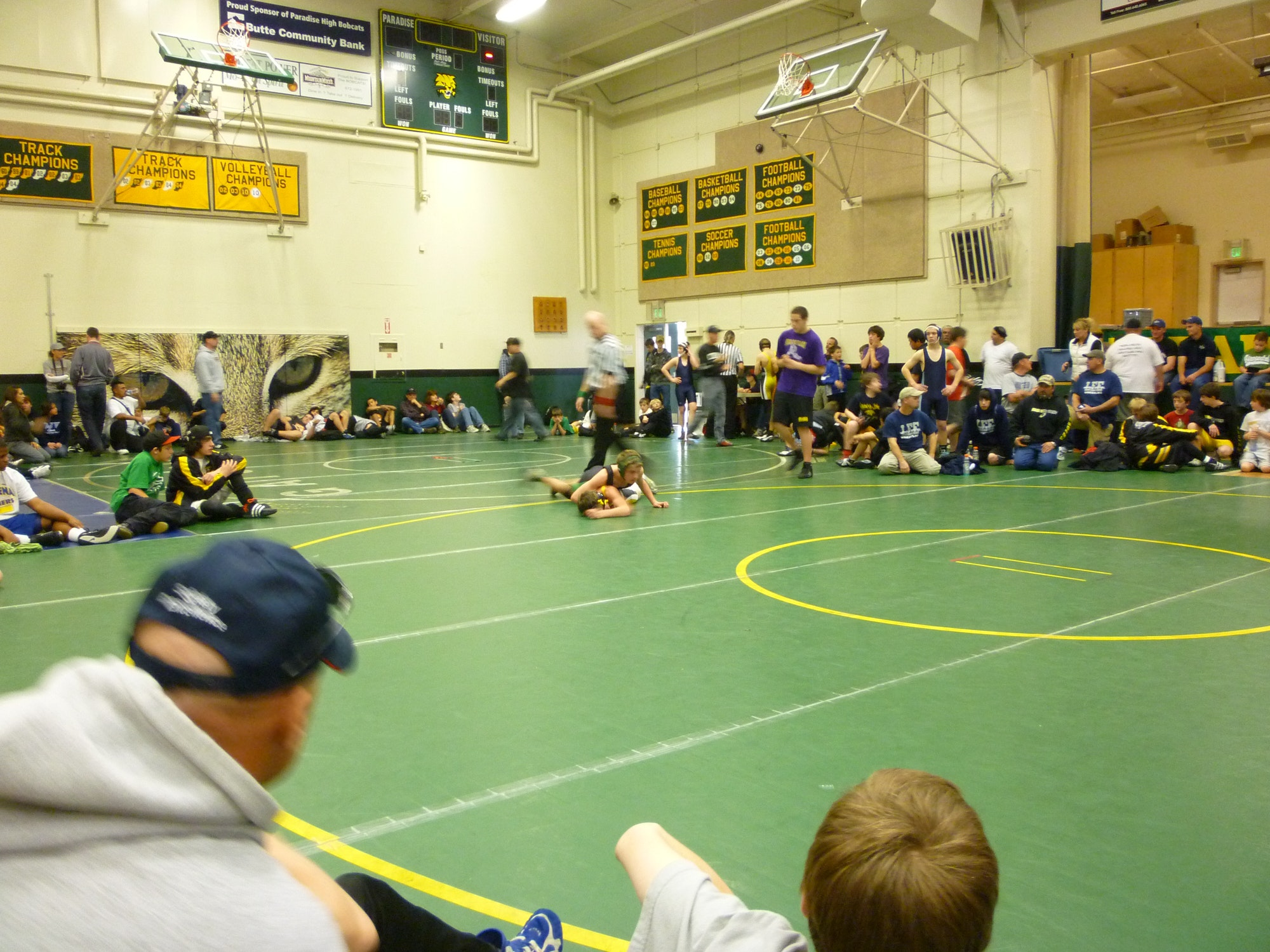 Adults and children watching a wresting match between two youth