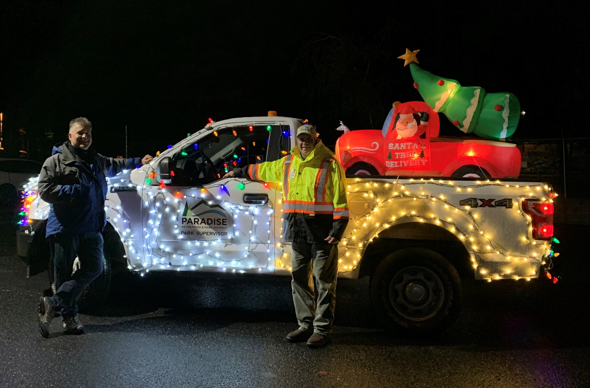 PRPD District Manager and Parks Supervisor smiling next to PRPD maintenance truck covered in bright Christmas lights