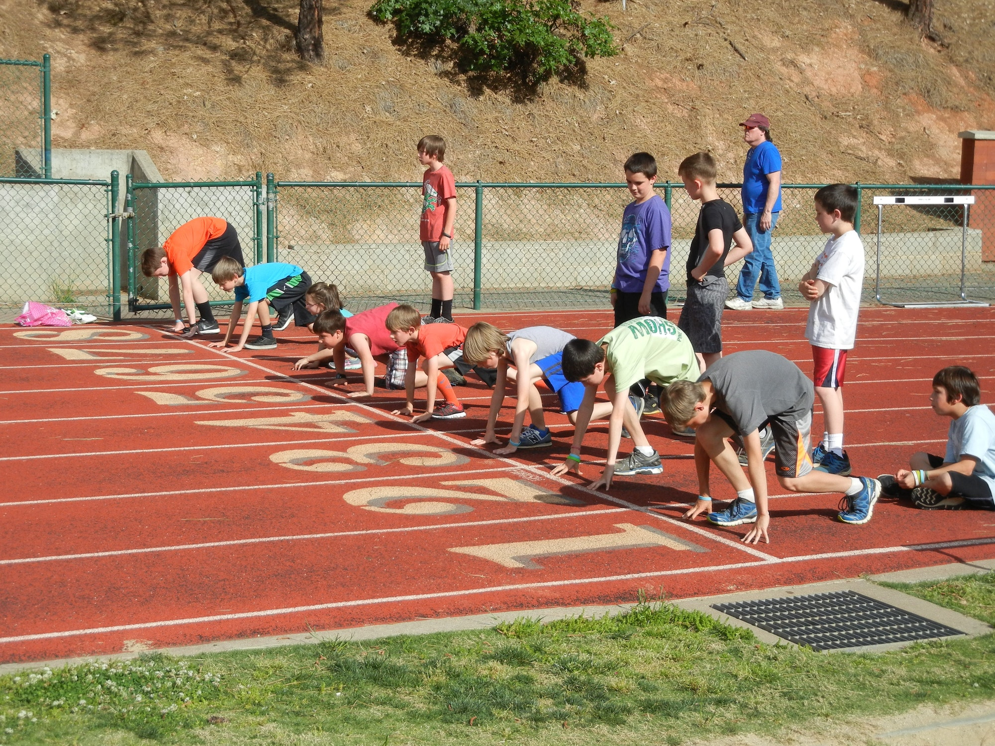 children at the starting line of a running track