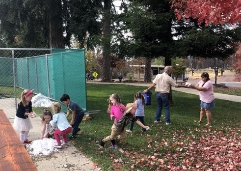 children playing in fall leaves at Terry Ashe Recreation Center in Paradise