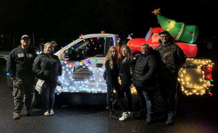 PRPD staff posing in front of a PRPD maintenance truck decorated with white and colorful Christmas lights and an inflatable santa driving a truck with a Christmas tree in the back