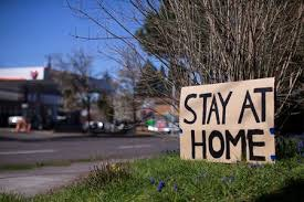 Picture of neighborhood with Stay at Home sign on tree.