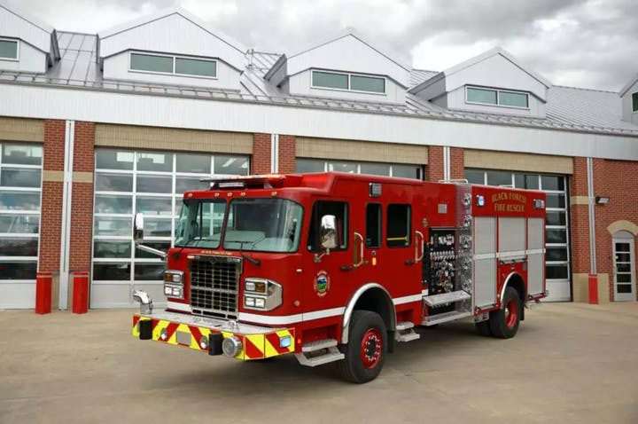 A red firetruck parked in front of a station