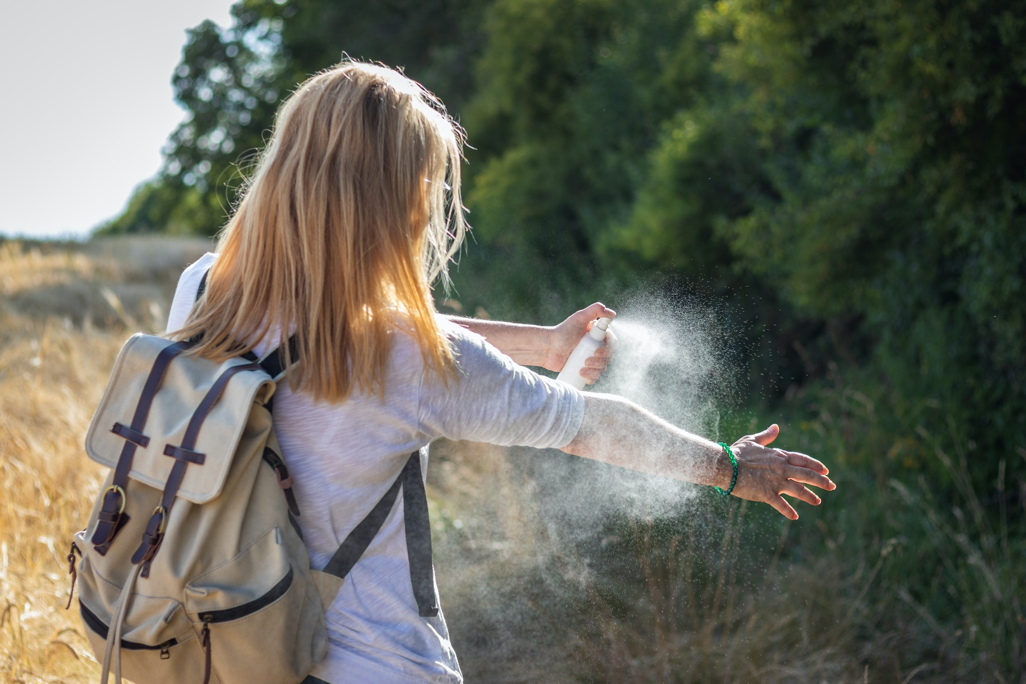 A person is outside in a grassy area near some green trees.  The person is facing away from the camera.  The person has long, light-colored hair, a white long-sleeve shirt, and a backpack.  The person is holding a container of bug repellent and spraying the exposed skin on their arm.