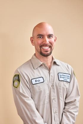 Smiling person with facial hair in tan District uniform.