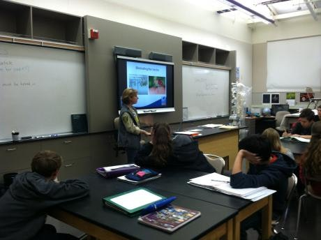 A person stands near a screen with a presentation while students sit at their desks.