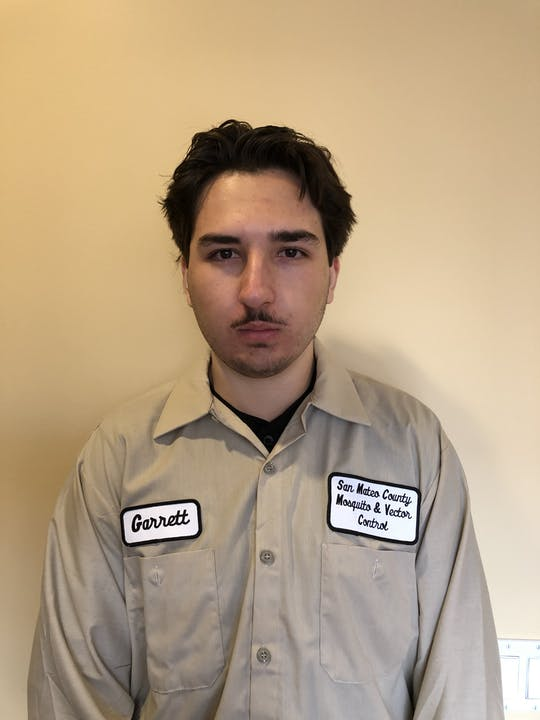 """Person in a light brown shirt with patches with the name """"Garrett"""" and """"San Mateo County Mosquito and Vector Control District""""  Person is standing in front of a tan background."""