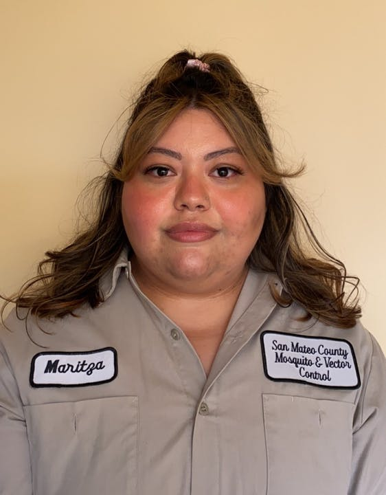 """Person in a light brown shirt with patches with the name """"Maritza"""" and """"San Mateo County Mosquito and Vector Control District""""  Person is standing in front of a tan background."""
