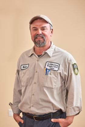 Smiling person with facial hair in tan District uniform and hat.