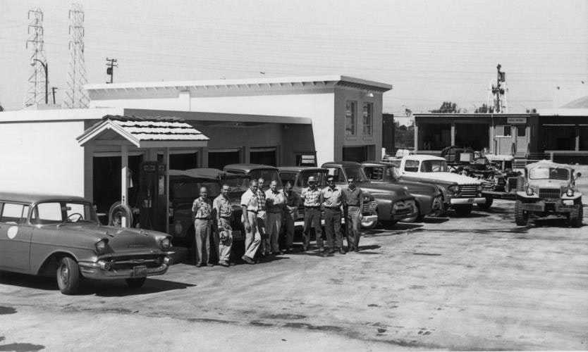 Grey and white photo of several buildings with vehicles from the mid-1900s and several people facing the camera in the parking lot
