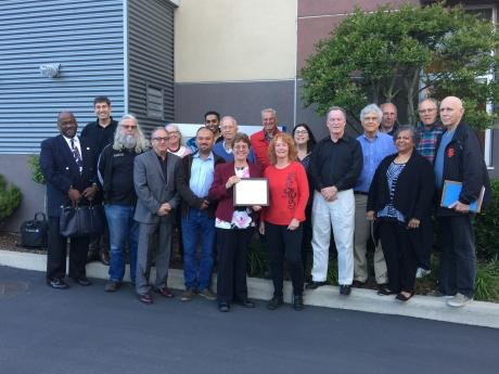 Group of people standing outside of the District office; one person in the front of the group is holding a certificate or plaque
