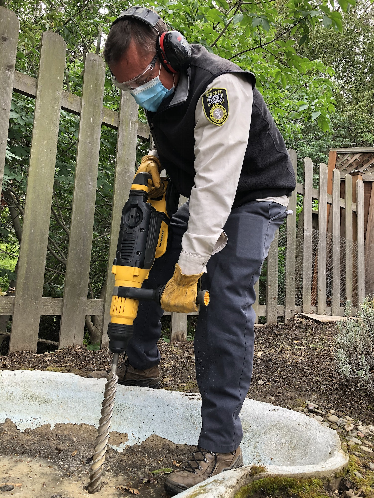 Person in tan, grey, and black uniform, with hearing protection, face mask, and work gloves.  Person is using a large drill with a thick, long bit to drill into a muddy concrete pond to create holes.