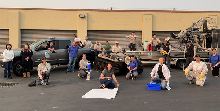19 people in front of a building. Many are in tan uniforms, some are holding equipment used for vector control. There is a pick-up truck, an Argo (a small vehicle used for accessing marsh areas, and an airboat (has a large fan on the back) on a trailer.