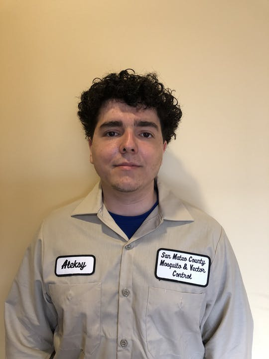 """Person in a light brown shirt with patches with the name """"Aleksy"""" and """"San Mateo County Mosquito and Vector Control District""""  Person is standing in front of a tan background."""