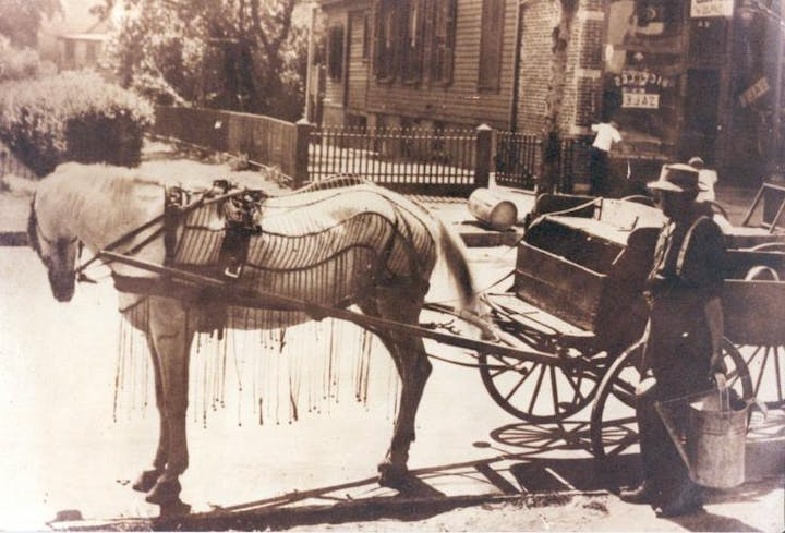Sepia photograph of a light colored horse hitched to a cart, with a person standing nearby holding a metal pail
